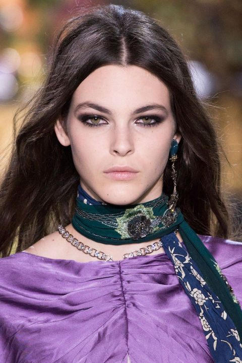 A model is wearing a purple top, a green scarf with metallic decorations and a single metallic earring