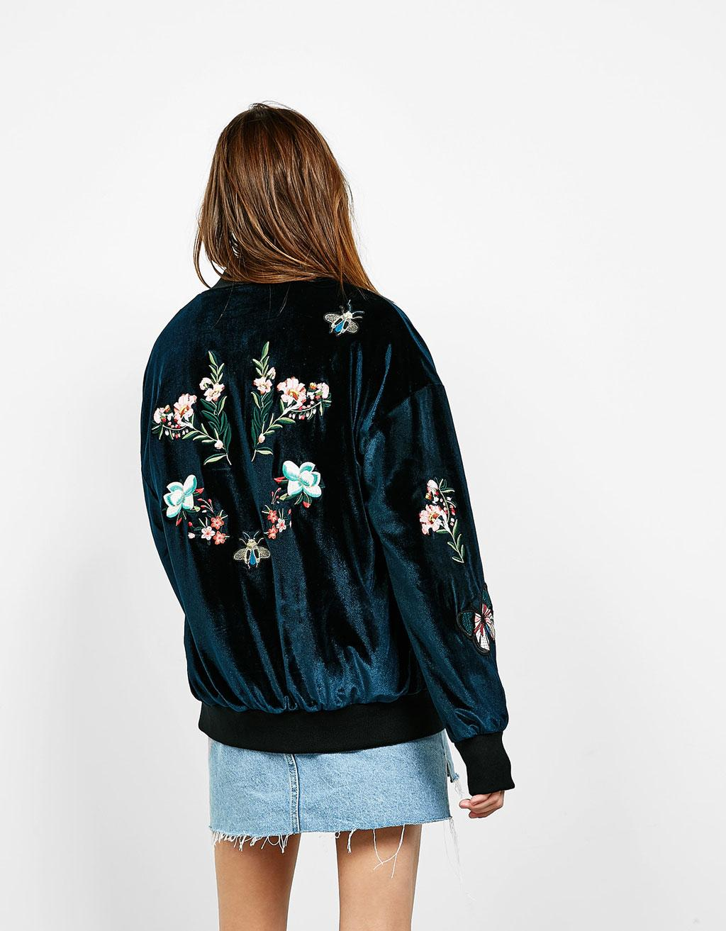 A model is wearing a velvet petrol bomber jacket with floral decorations and a denim mini skirt
