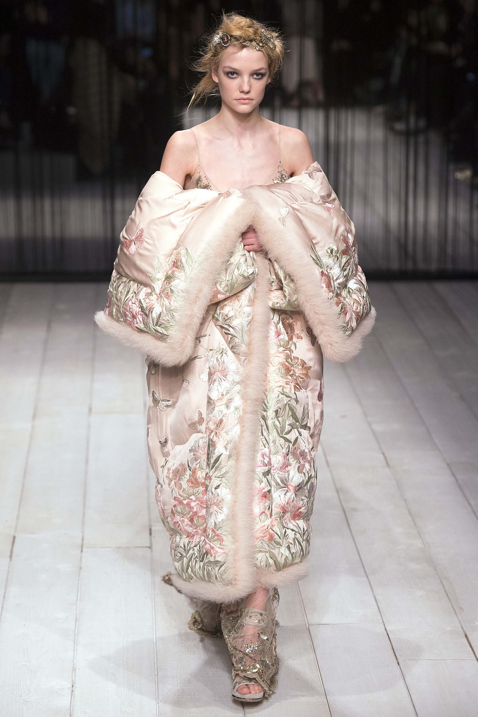 From Alexander McQueen fashion show: a model is wearing an extravagant extra long floral off-the-shoulders puffer coat