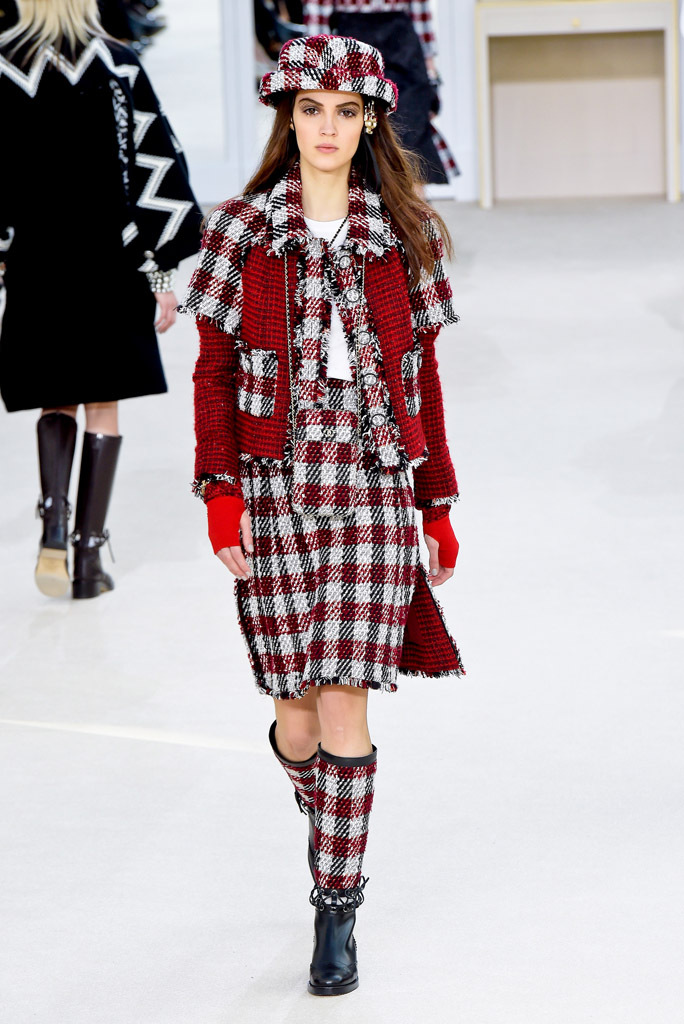 A model is wearing an outfit made by boots, a skirt, a jacket and a hat, all in tweed and checks