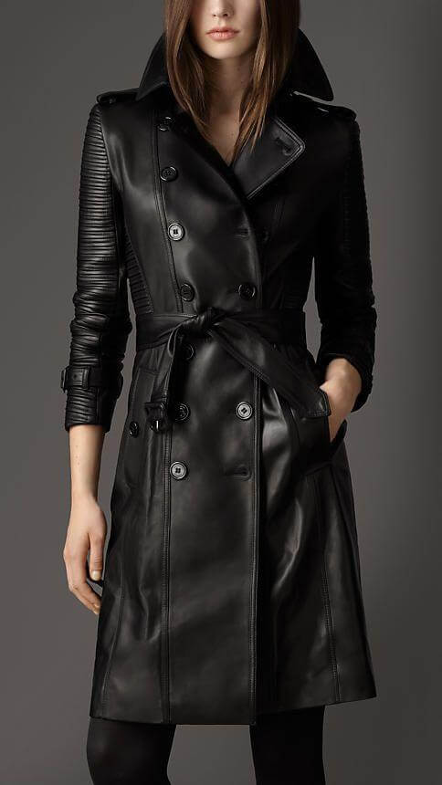 A model in a black leather trench coat in a total black outfit