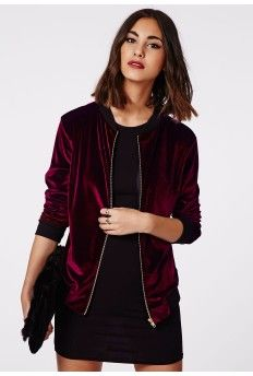 A model is wearing a burgundy velvet jacket and a black mini dress
