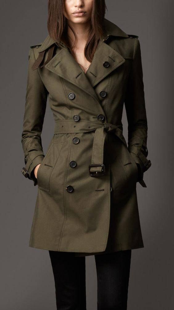 A model is wearing a dark cold khaki trench coat with black pants