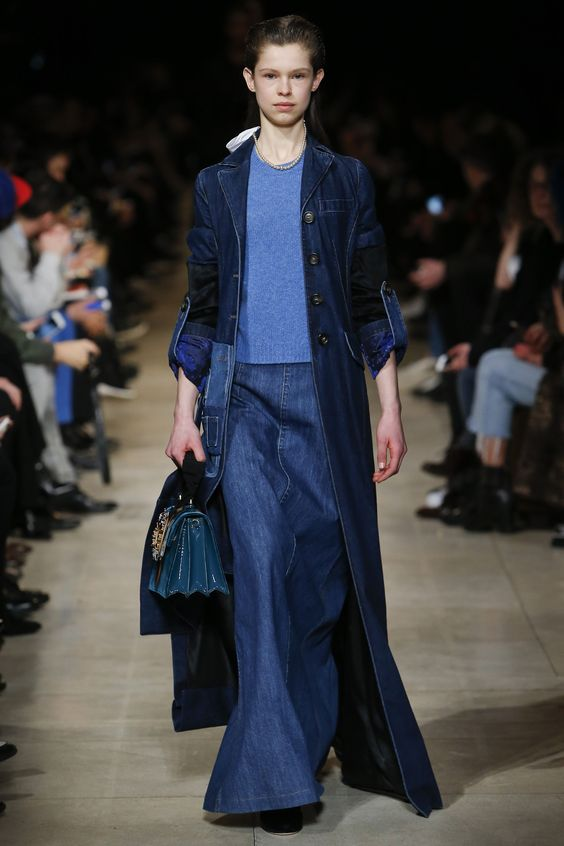 A model is wearing a total denim look, with an extra long coat, all in total blue