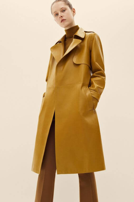A model is wearing a spicy mustard yellow leather coat with dark camel pants and turtleneck