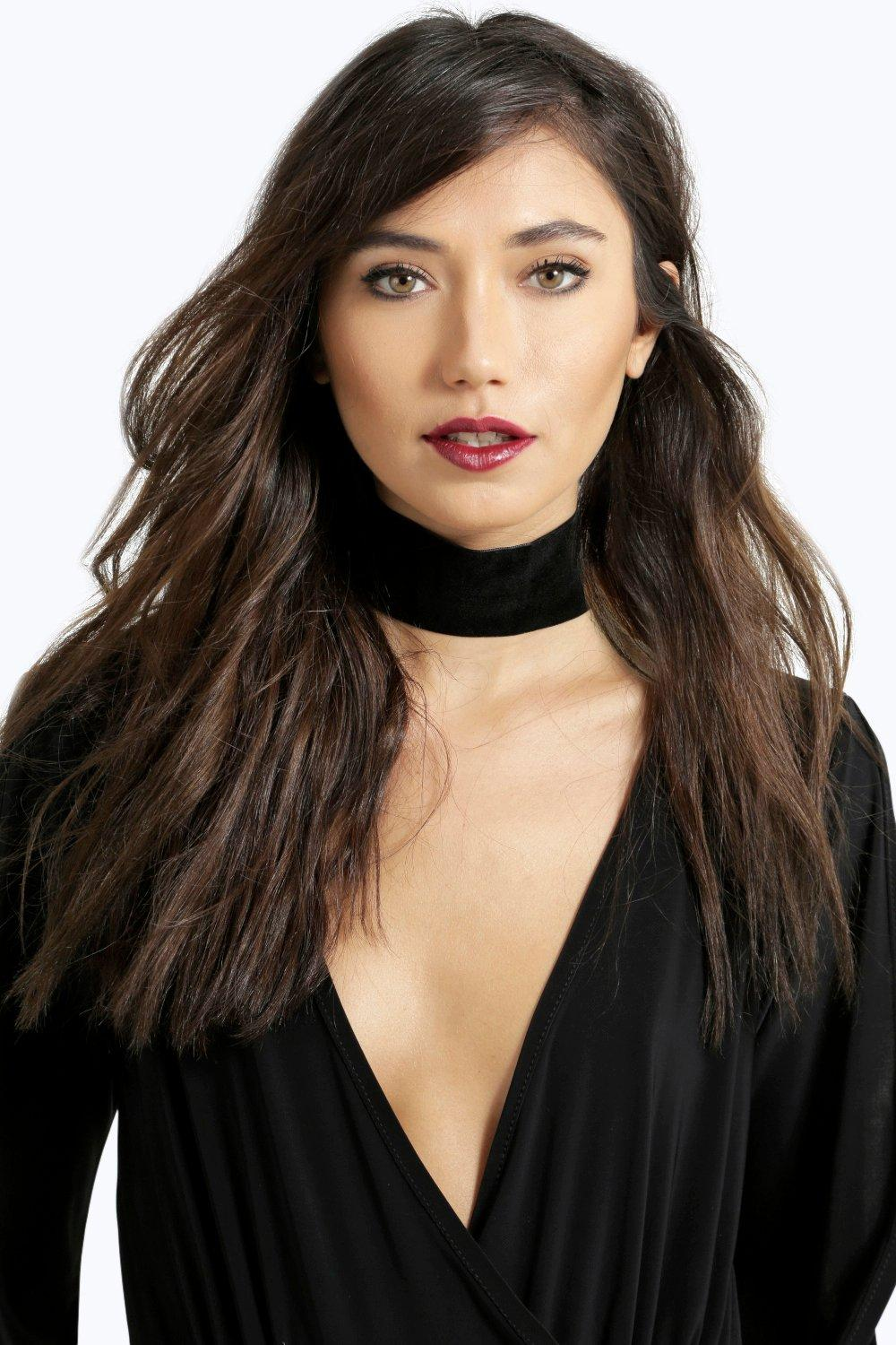A model is wearing an extra wide black choker and a black v-neck top