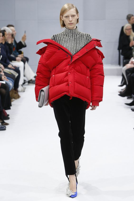 Balenciaga's bright red oversized puffer coat: dressed up with black pants, black and white checked turtleneck, silvery detailed high heels and a light gray clutch. A great example of a mixture between an elegant outfit and a sporty piece of clothing.
