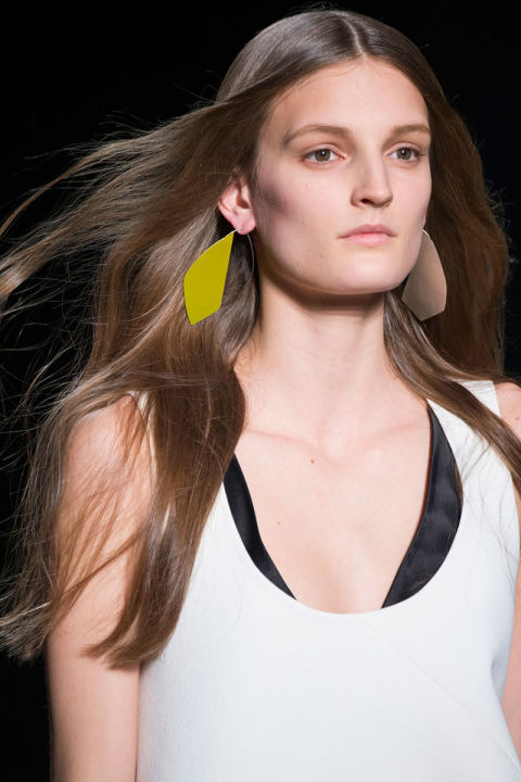 A model is wearing a black and white top, and yellow clean cut earrings