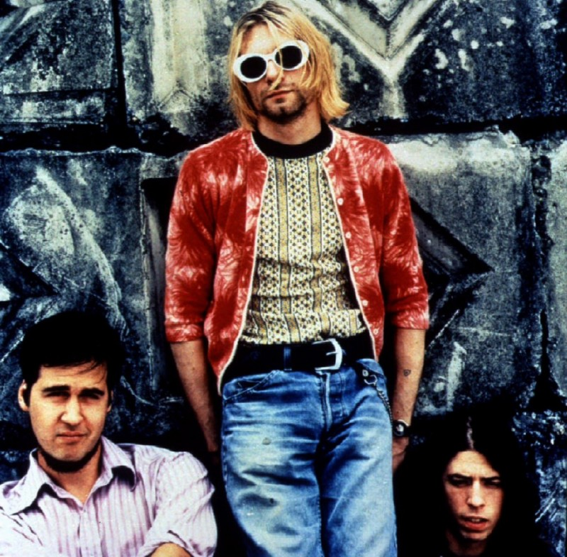 Grunge band Nirvana, with Kurt Cobain wearing light blue denim jeans, geometric pattern sweater and velvet jacket