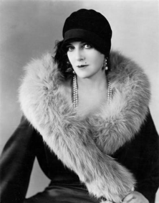 A perfect look from the roaring twenties: a hat that covers short hairstyle, a long pearl necklace, and a coat with furry details.