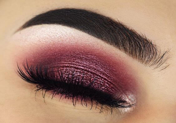 Photo of a closed eye with pink eyeshadow over the lid and silver eyeshadow highlighting the brow bone and inner corner