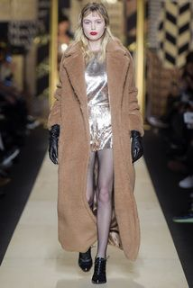A model on the runway is wearing a long camel coat, a shiny metallic dress, and black oxford shoes