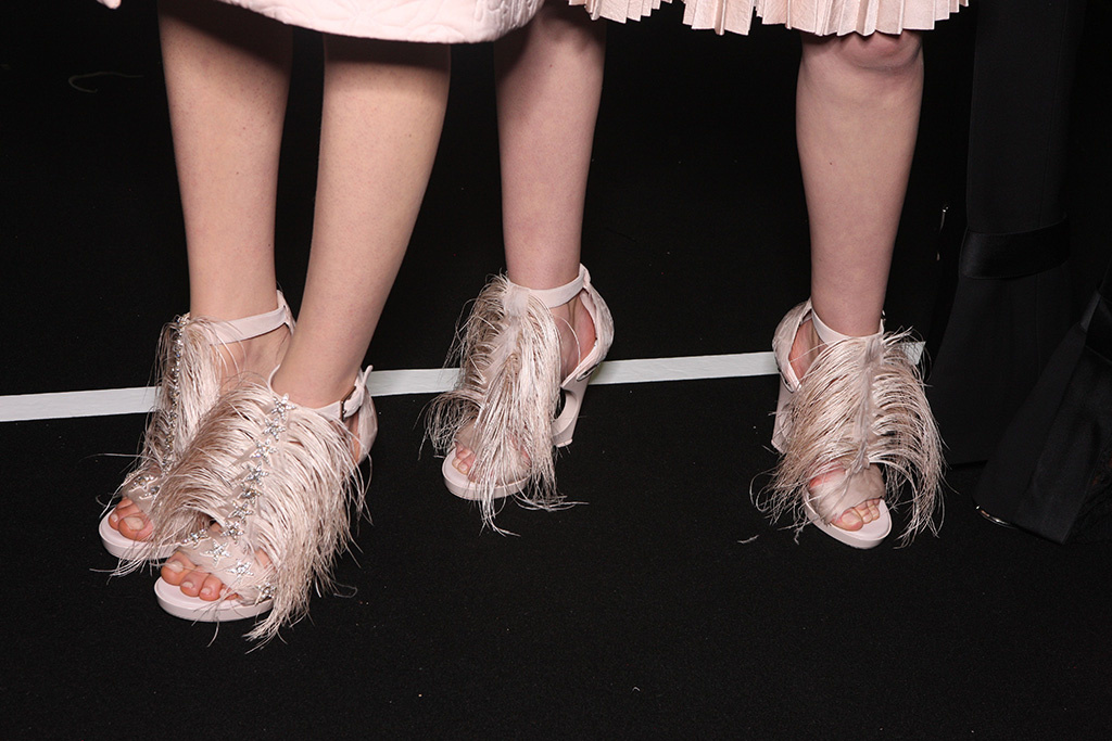 Two models are wearing fringed heels from Alexander McQueen