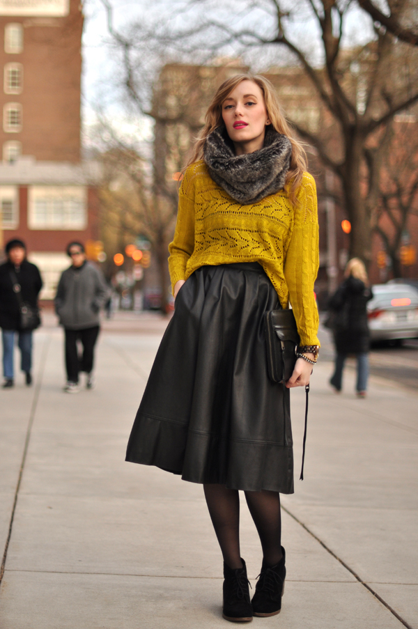 A woman is wearing a fur collar, a yellow mustard pullover, a wide gray skirt, and black ankle boots and a black clutch