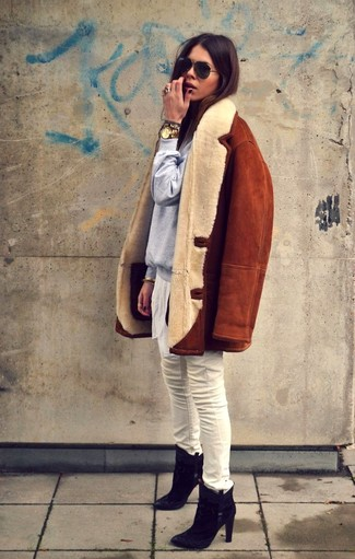 Elegant outfit with shearling coat: oversize coat in camel nuance, white pants, golden accessories and medium heels ankle black boots in suede, with a pointy toe. Everything is finished off with golden accessories, such as a very big watch.