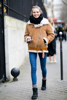 A woman is wearing a big shearling coat, blue skinny jeans, a black scarf and black combat boots with gray socks
