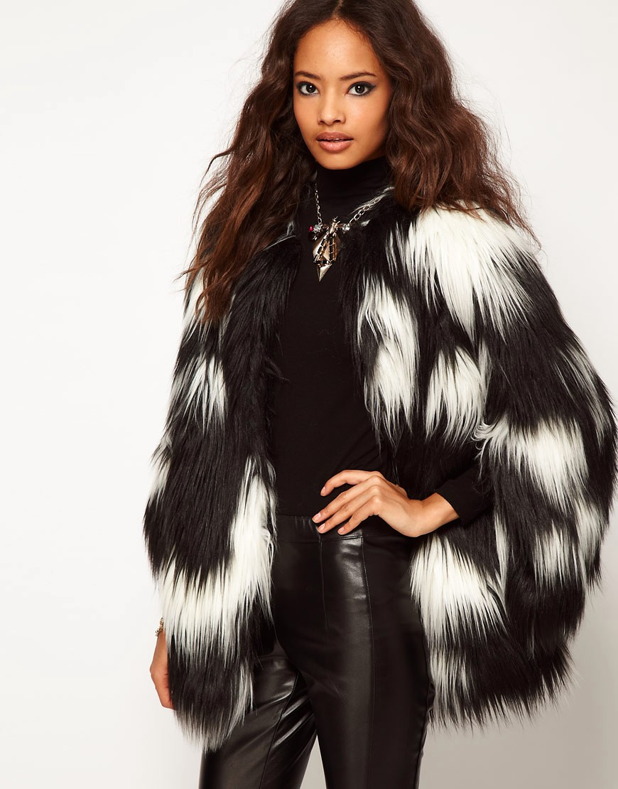 A woman is wearing black leather pants and a black turtleneck with an oversize long-haired black and white striped fur coat