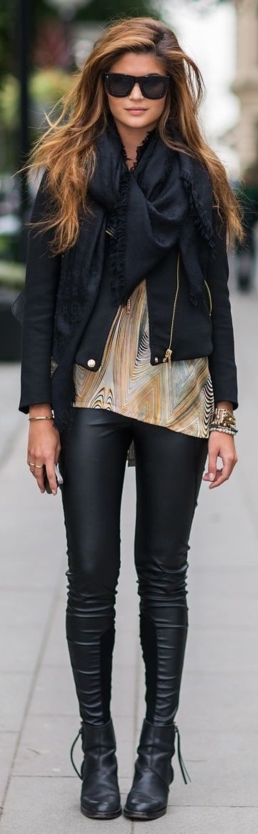 Woman in black leather pants, patterned top, black scarf and black jacket with black leather boots