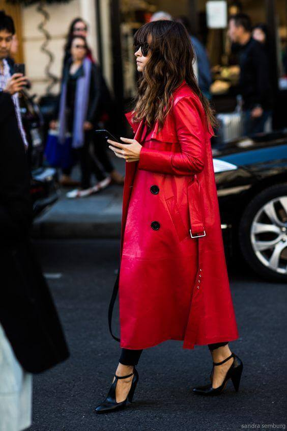 A woman is wearing an ankle length bright red trench coat with black heels and sunglasses