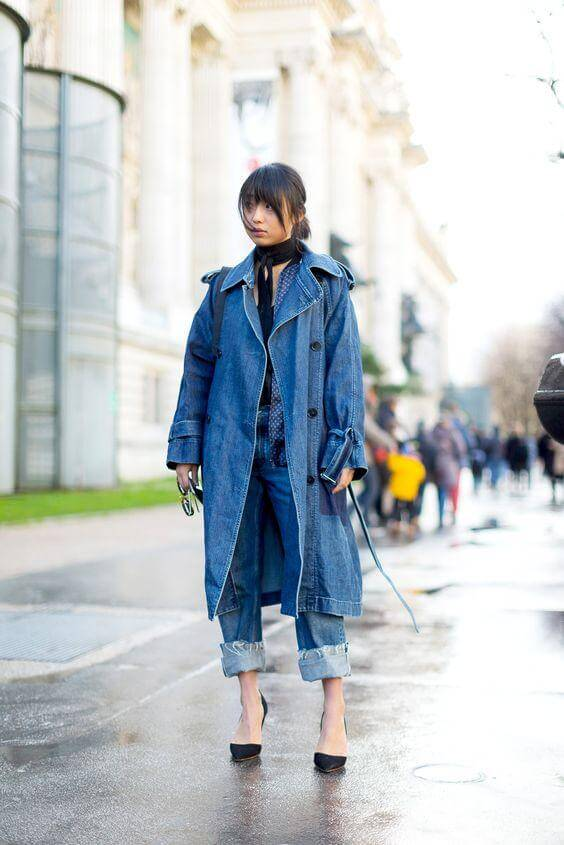 A woman is wearing denim jeans, an oversize denim coat, a black scarf and black stilettos