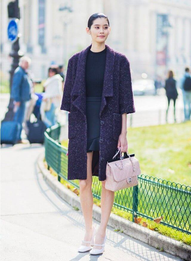 Woman in long tweed coat and pink handbag