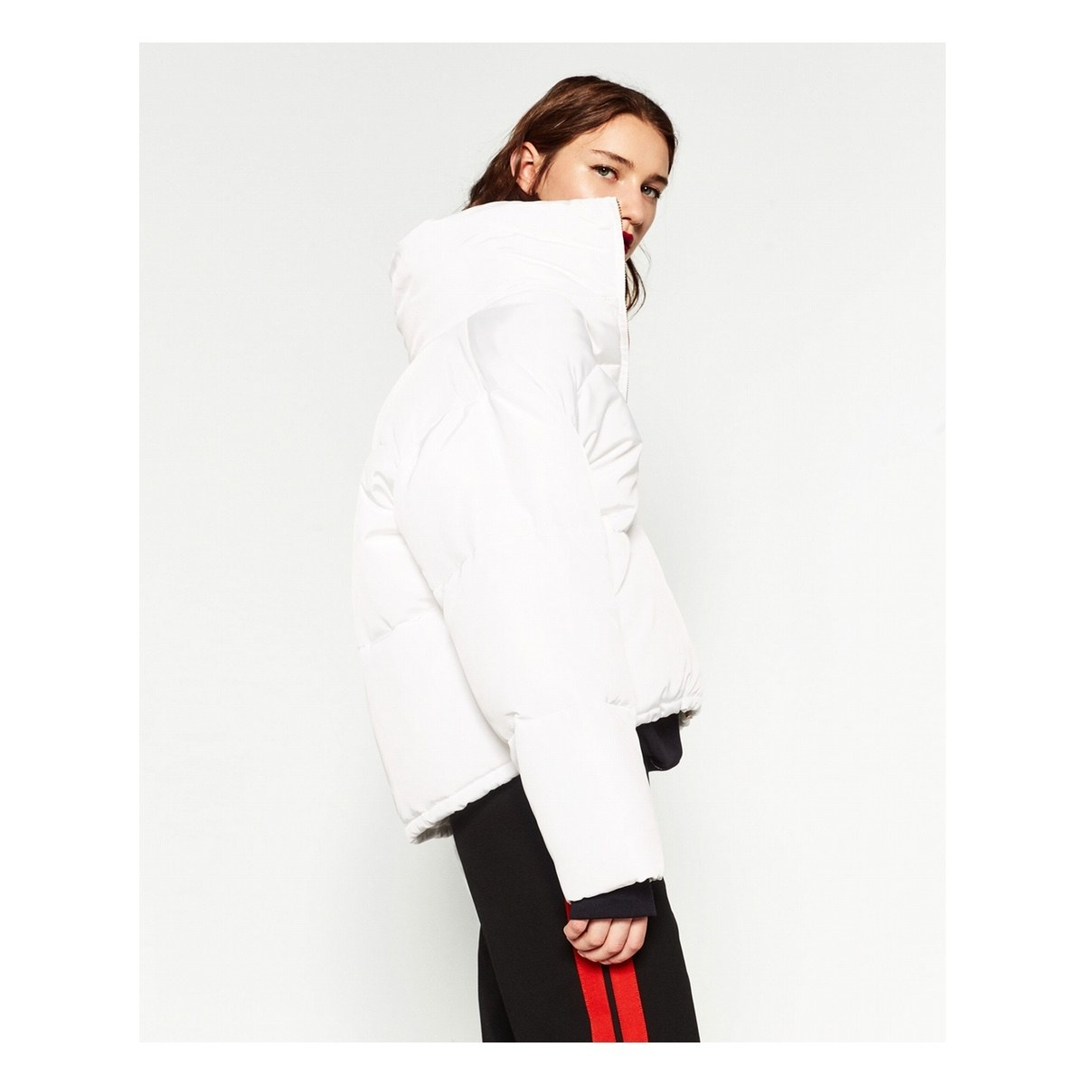 The fast fashion option: puffer coat from Zara in total white, oversize neck, paired with black sleeves underneath and sporty pants with red details to spice up the look.