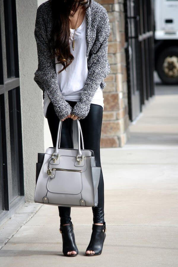 Woman on the sidewalk wearing black leather pants, long white T-shirt, gray cardigan with black peep-toe shoes and gray handbag