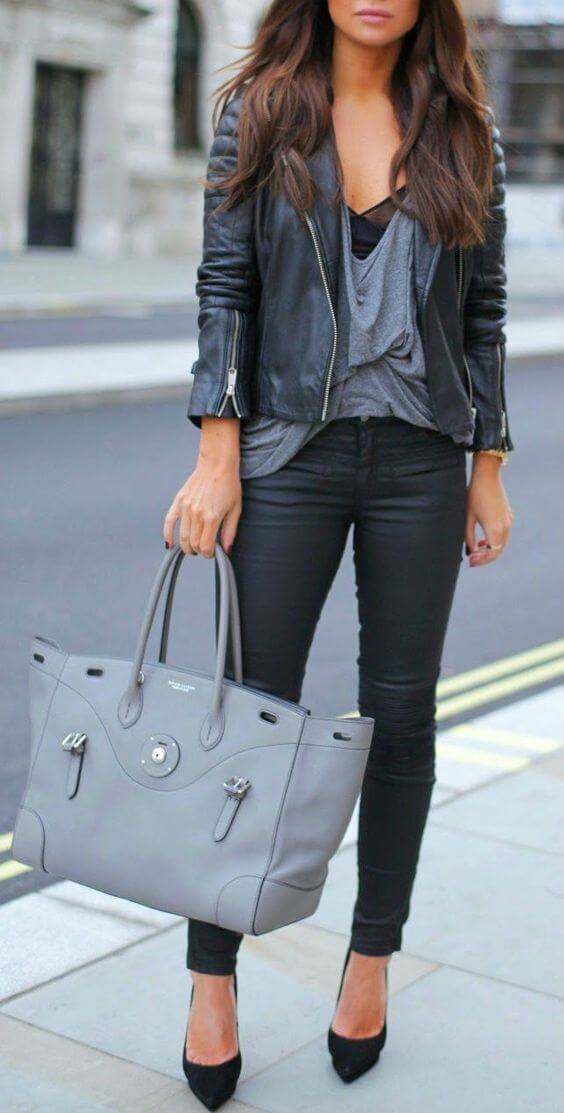 Woman on the sidewalk wearing black skinny jeans, gray slouchy vest and black leather jacket with black pointy heels and gray handbag