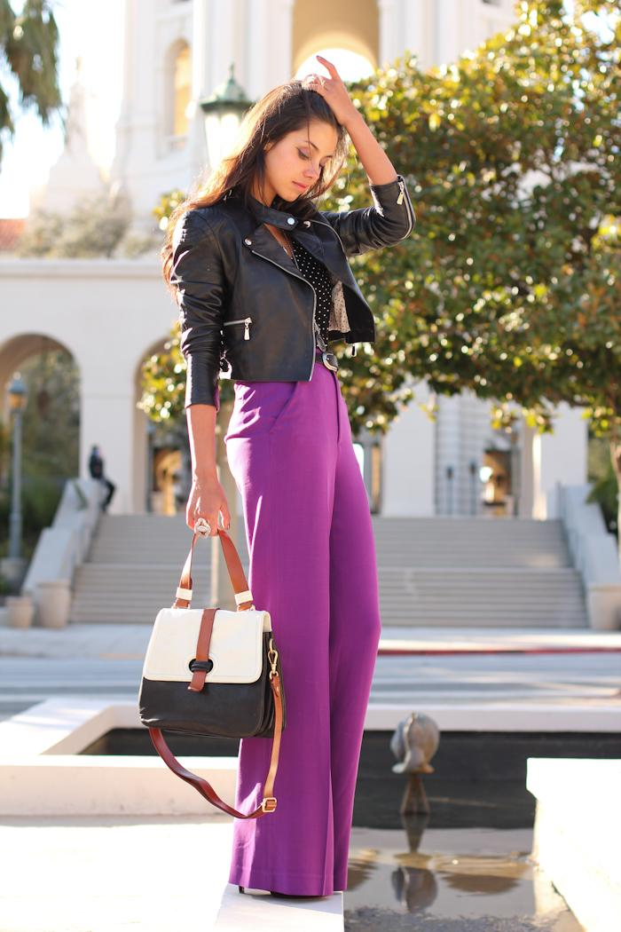 A woman is wearing a black leather jacket with long palazzo pants in deep purple, and a black and white handbag with brown details
