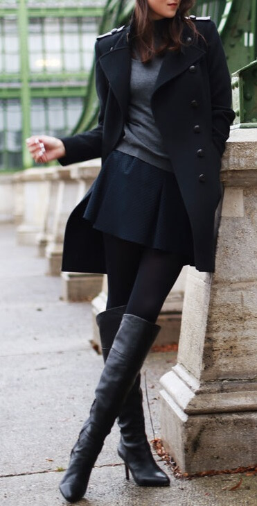 Woman wearing a black miniskirt, gray top, black coat and black knee-high boots