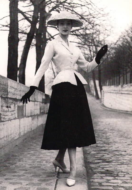 Woman wearing a black skirt and a white jacket with rounded hips and shoulders, white medium heels, black gloves, and a white hat