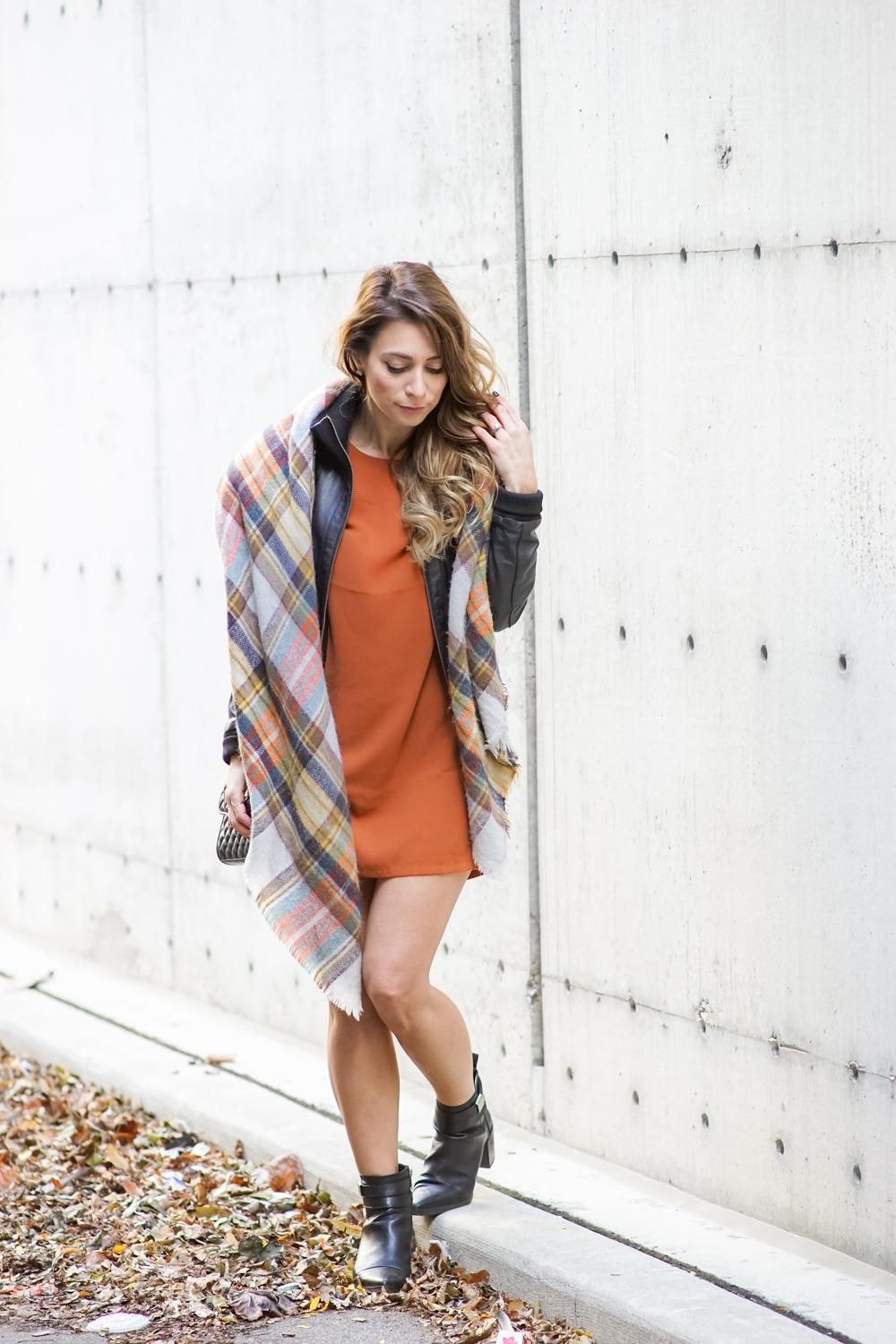 A woman is wearing a cardigan decorated with tartan style checks, an orangey minidress and black leather ankle boots