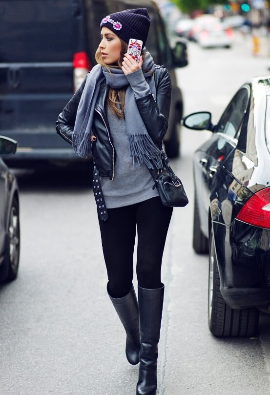 Woman wearing a gray top, gray scarf, black leather jacket, black tights and black leather boots