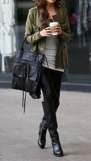 Woman wearing a gray top, khaki military-style jacket, black tights and black leather boots