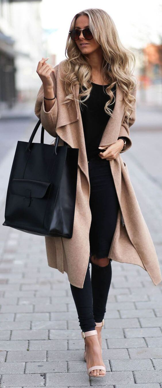 A woman is wearing a long beige coat with a black t-shirt and black distressed pants, with a black leather bag and vintage pink sandals