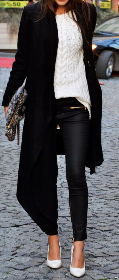 Woman wearing a long black trench coat, a white pullover, black pants and white stilettos