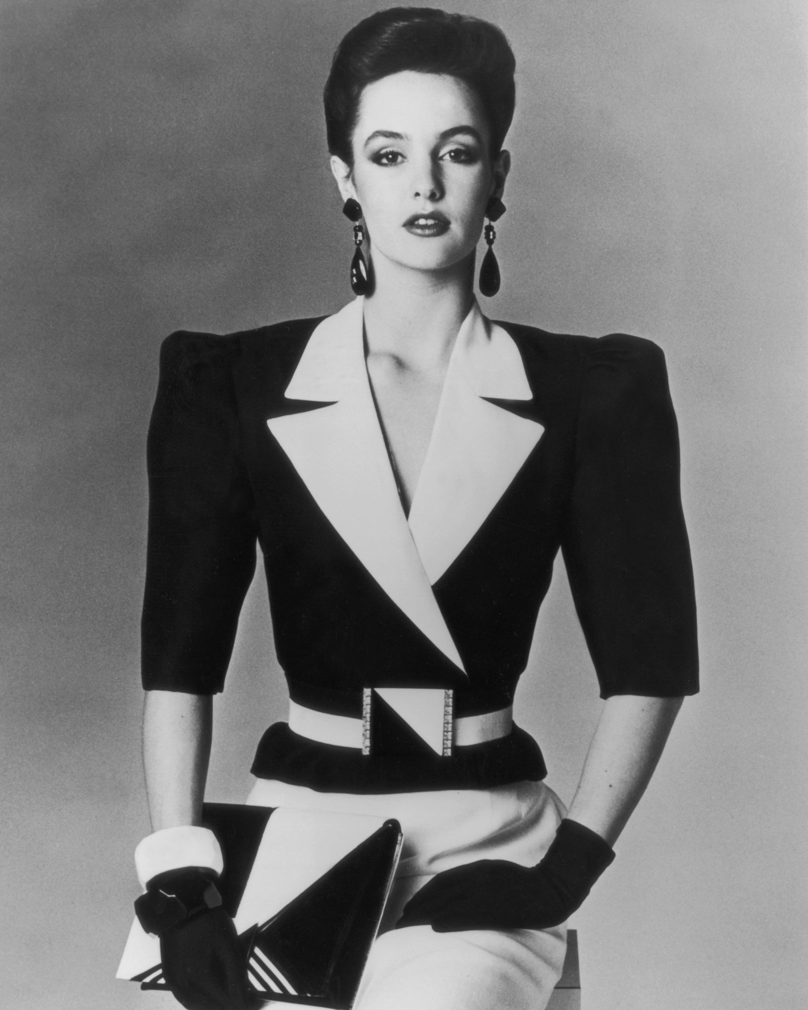 A woman is wearing an all black and white outfit: a jacket with extra wide shoulders, a white bottom, black gloves, black and white clutch and earrings