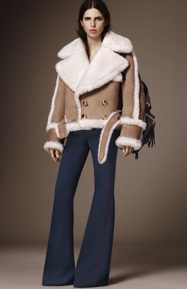Seventies inspiration meets western and ranch style, for this shearling coat outfit: an extremely oversize coat with fluffy white furry inside, paired with blue flared wide leg pants and a fringed backpack.