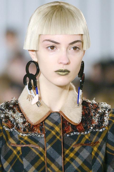 Woman wearing big surrealistic earrings