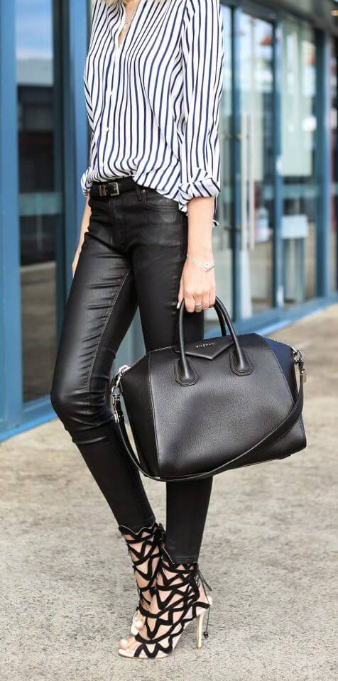 Woman wearing black leather pants, striped button-down shirt, graphic cut-out statement heels and a black leather bowler bag