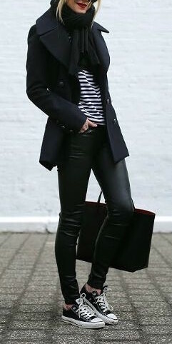 Woman wearing black leather pants, striped Breton shirt, black scarf, navy blue coat and black Converse sneakers