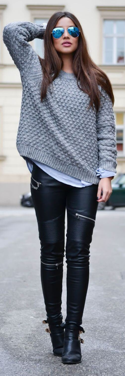 Woman wearing black leather pants with zip detailing, gray jersey and black leather boots