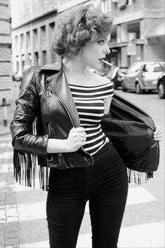 Woman wearing black skinny pants, an off-the-shoulder black and white striped t-shirt, and a fringed leather jacket