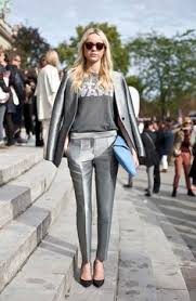 A woman is wearing a metallic silver outfit of jacket, pants, a gray t-shirt and black heels
