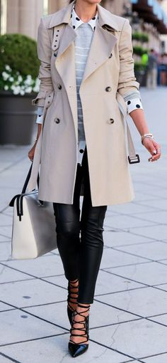 Woman in a polka dot black and white shirt with a grey and white striped pullover, black leather skinny pants, black pointy toe gladiator-style heels sandals, and a beige structured trench coat