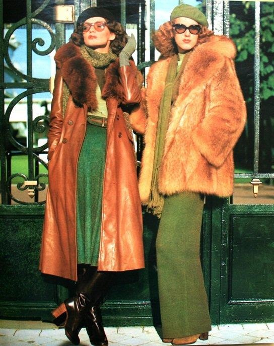 A woman on the left is wearing a long leather jacket with a fur collar on top of a green skirt, finished off with black leather boots and a black hat. On the right, another woman is wearing olive green wide leg pants, camel boots, and an oversize fur coat
