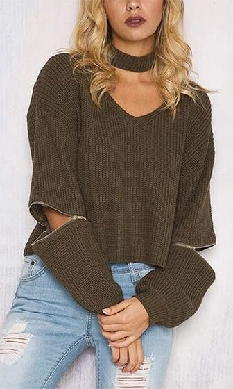 A woman is wearing brown sweater with jeans