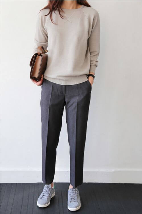 A woman is wearing grey pants with a beige sweater