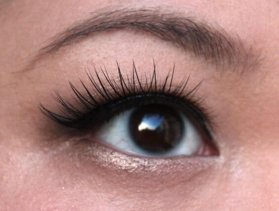 Close-up of false eyelashes applied to an Asian eye
