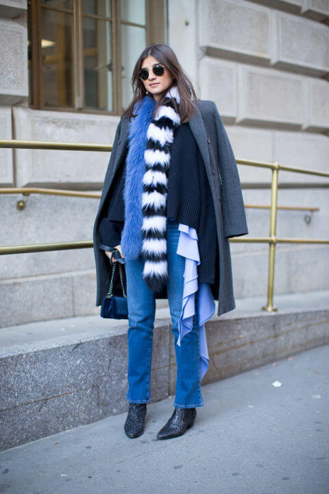 Dark haired woman in denims and a knee-length coat with faux fur scarves